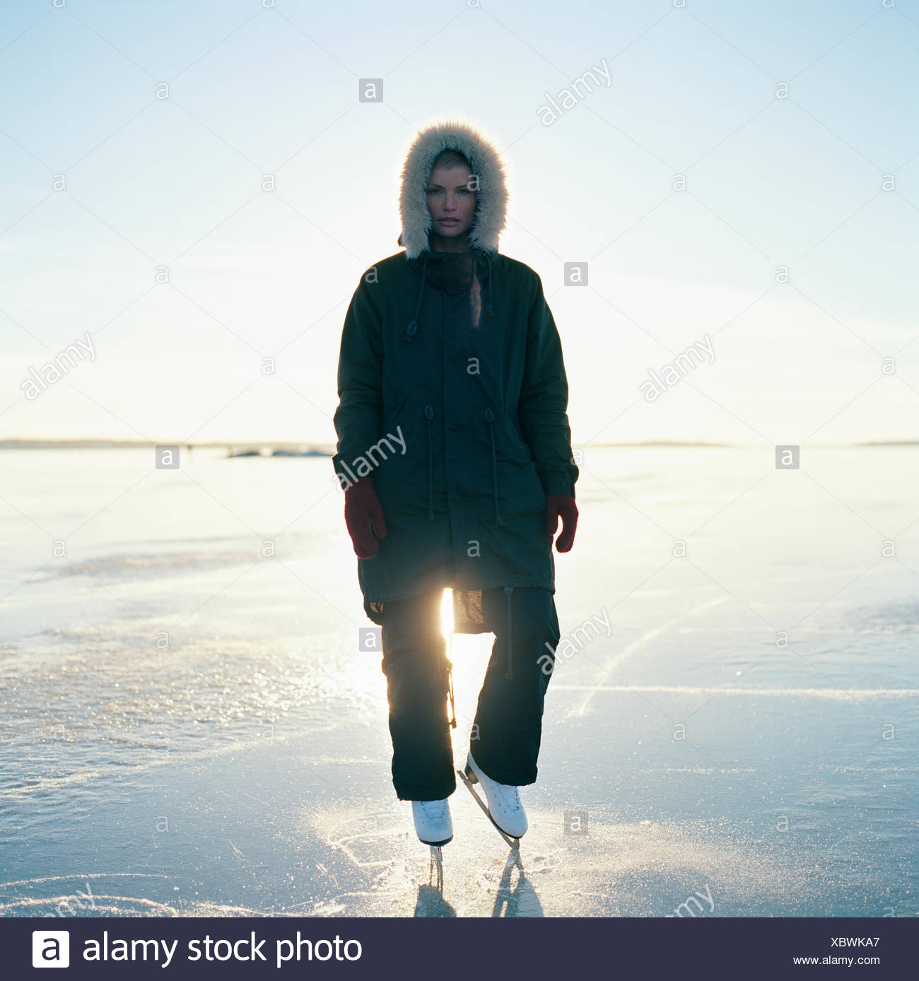 Sweden, Uppland, Varmdo, Bjorno, Mid adult woman in ice skates standing on frozen lake - Stock Image