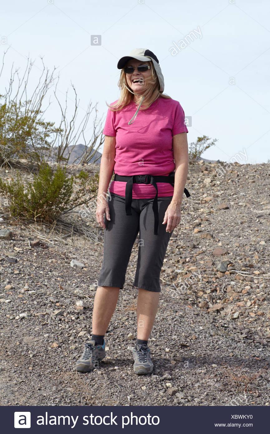 Portrait of senior female hiker on arid hill - Stock Image