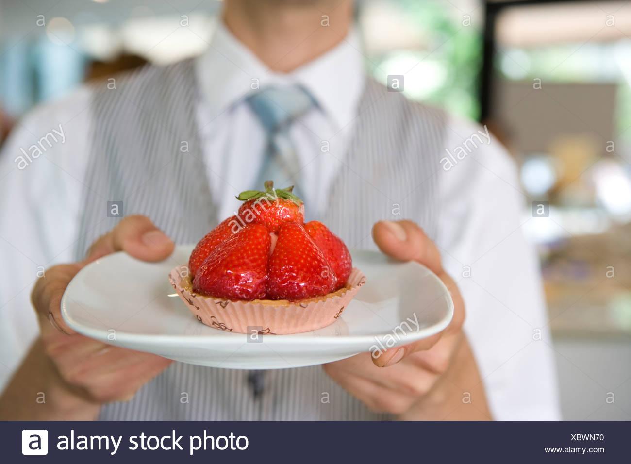 Waiter with strawberry tart, close-up of tart - Stock Image