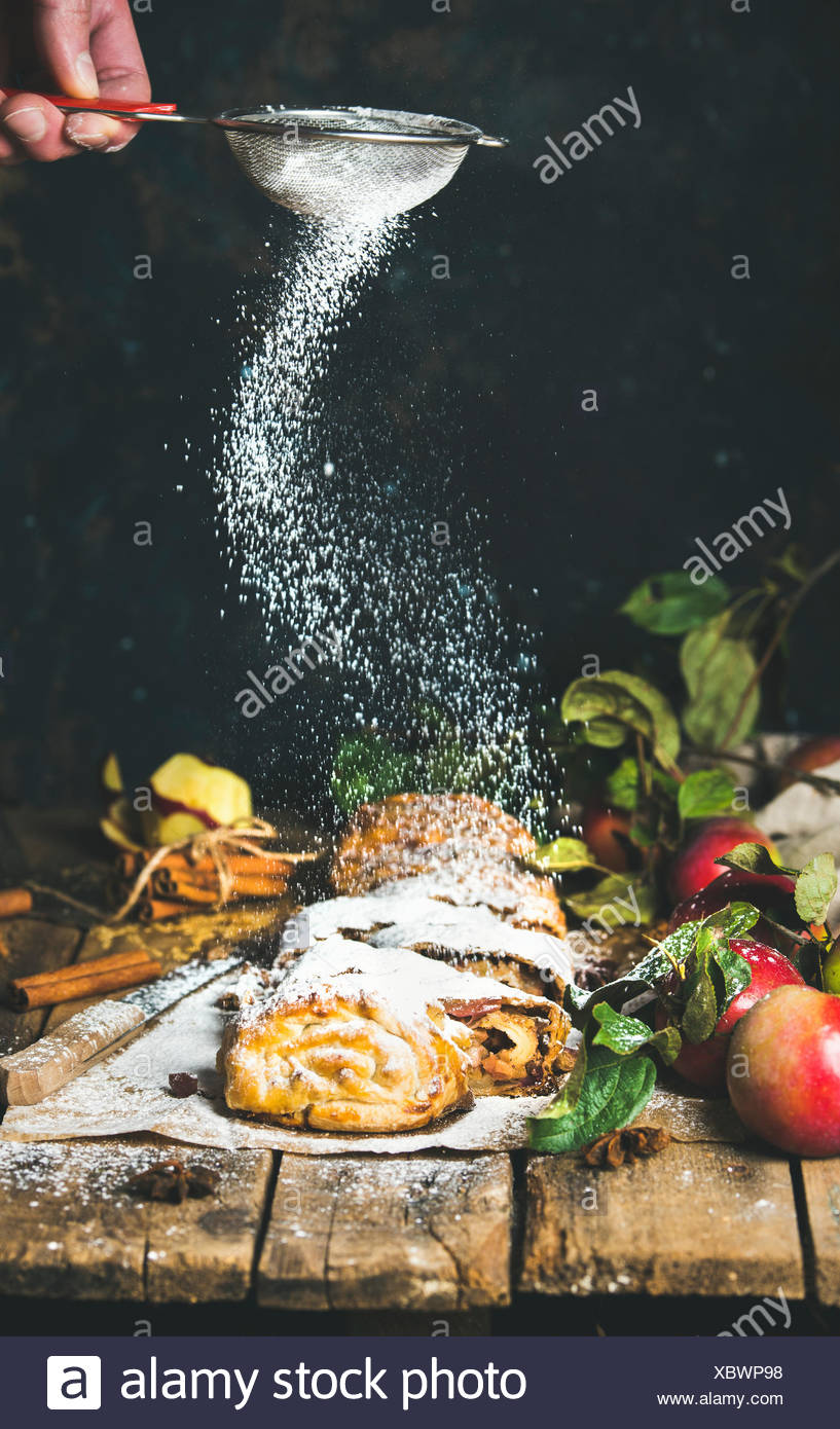 Man's hand with sieve sprinkling sugar powder on apple strudel cake with cinnamon and fresh apples on rustic wooden table, dark - Stock Image