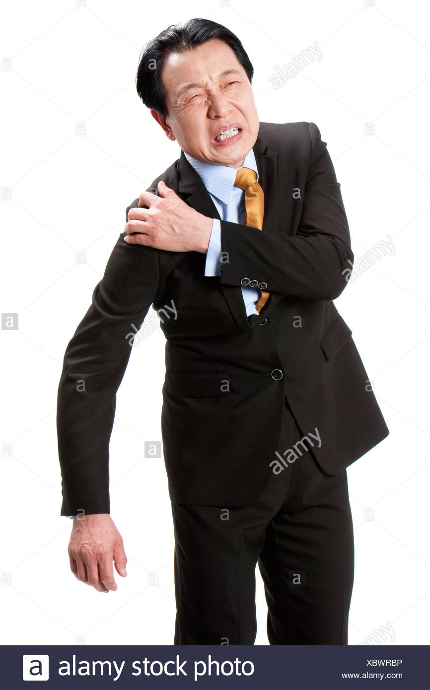 Senior businessman suffering from pain on shoulder - Stock Image