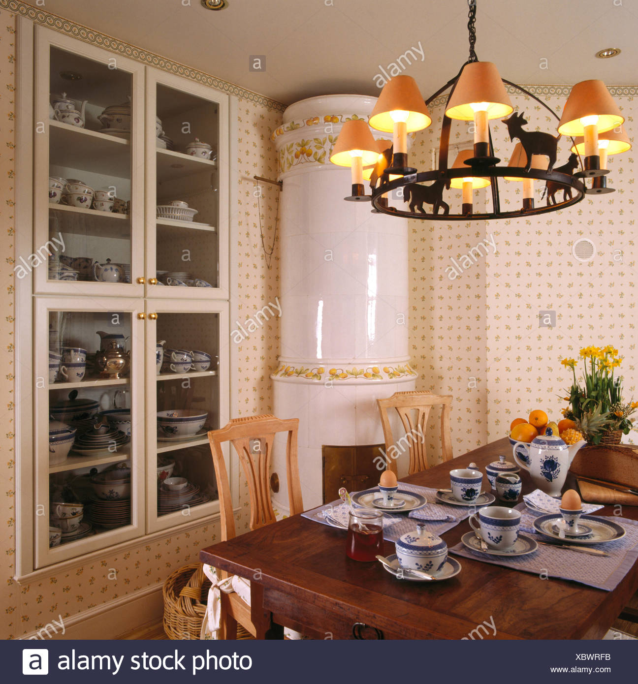 Shades on wrought iron ceiling light above table set for breakfast in dining room with large white ceramic stove - Stock Image