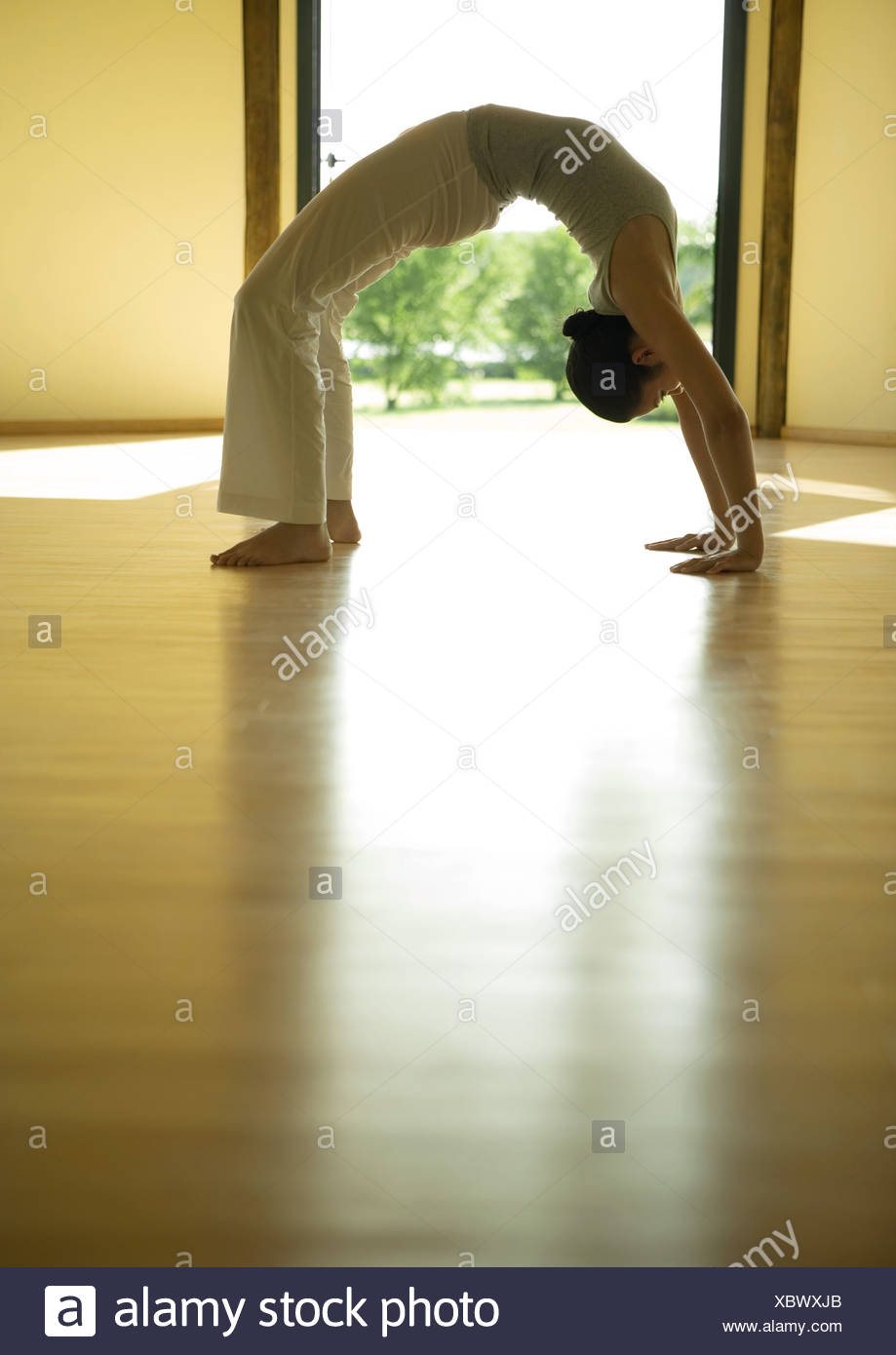 Woman doing bridge position, side view Stock Photo
