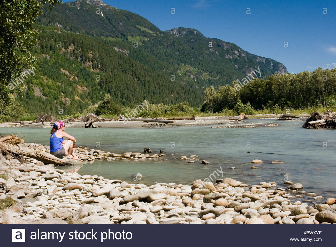 A woman in her late twenties cools off at the Squamish River after a hike near Squamish, British Columbia, Canada. - Stock Image