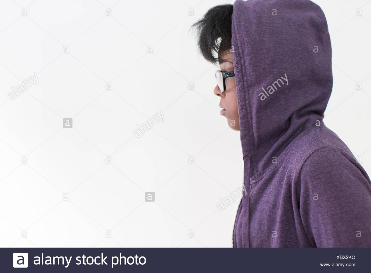Studio profile portrait of young woman wearing hoody - Stock Image