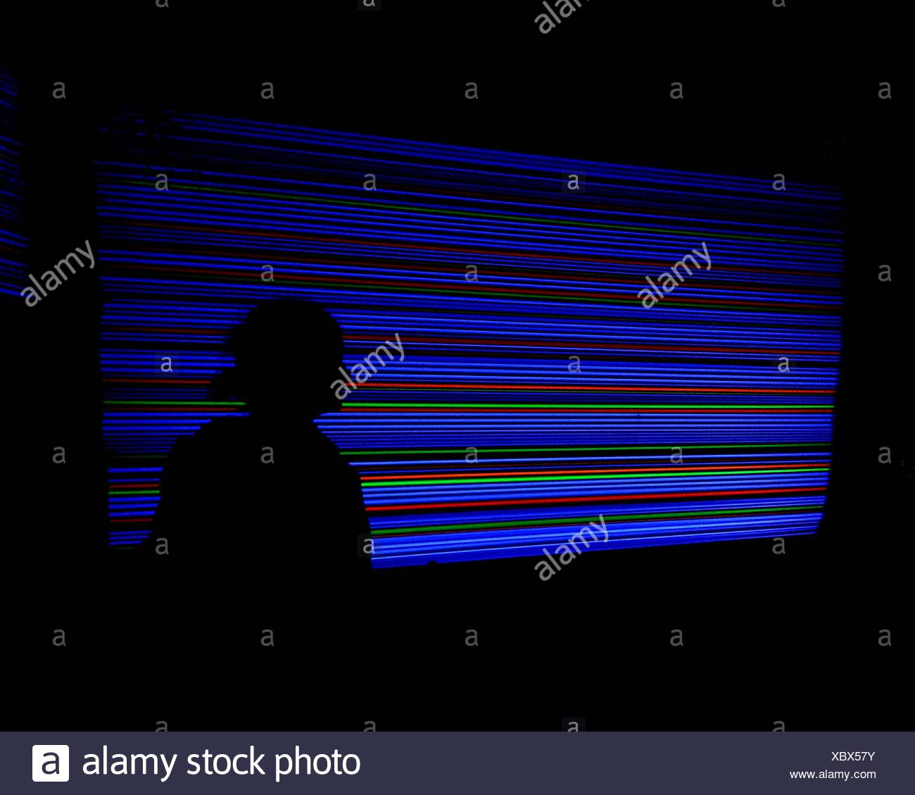 Silhouette Man Against Illuminated Colorful Neon Lights - Stock Image