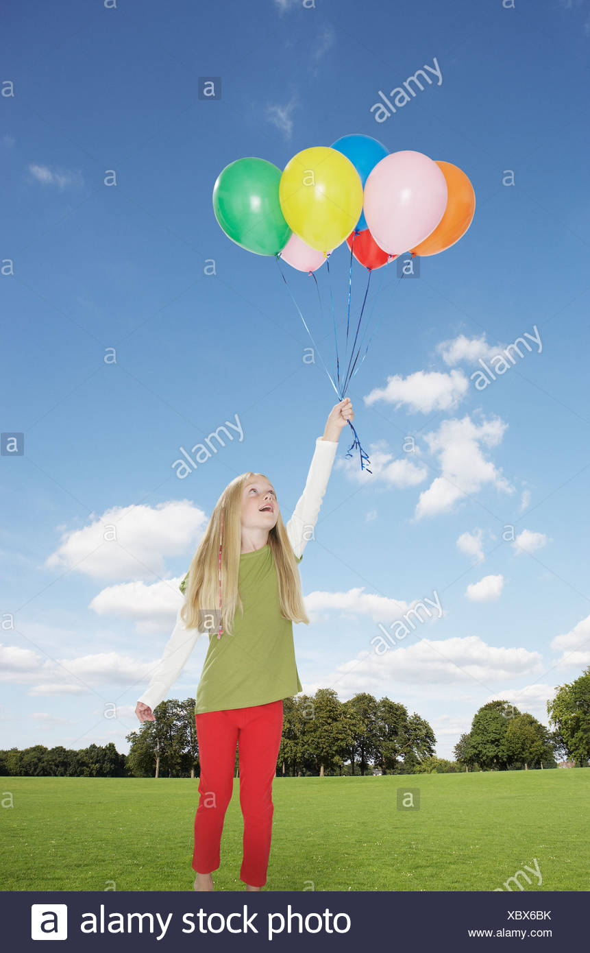 Young girl outdoors holding balloons at a park - Stock Image