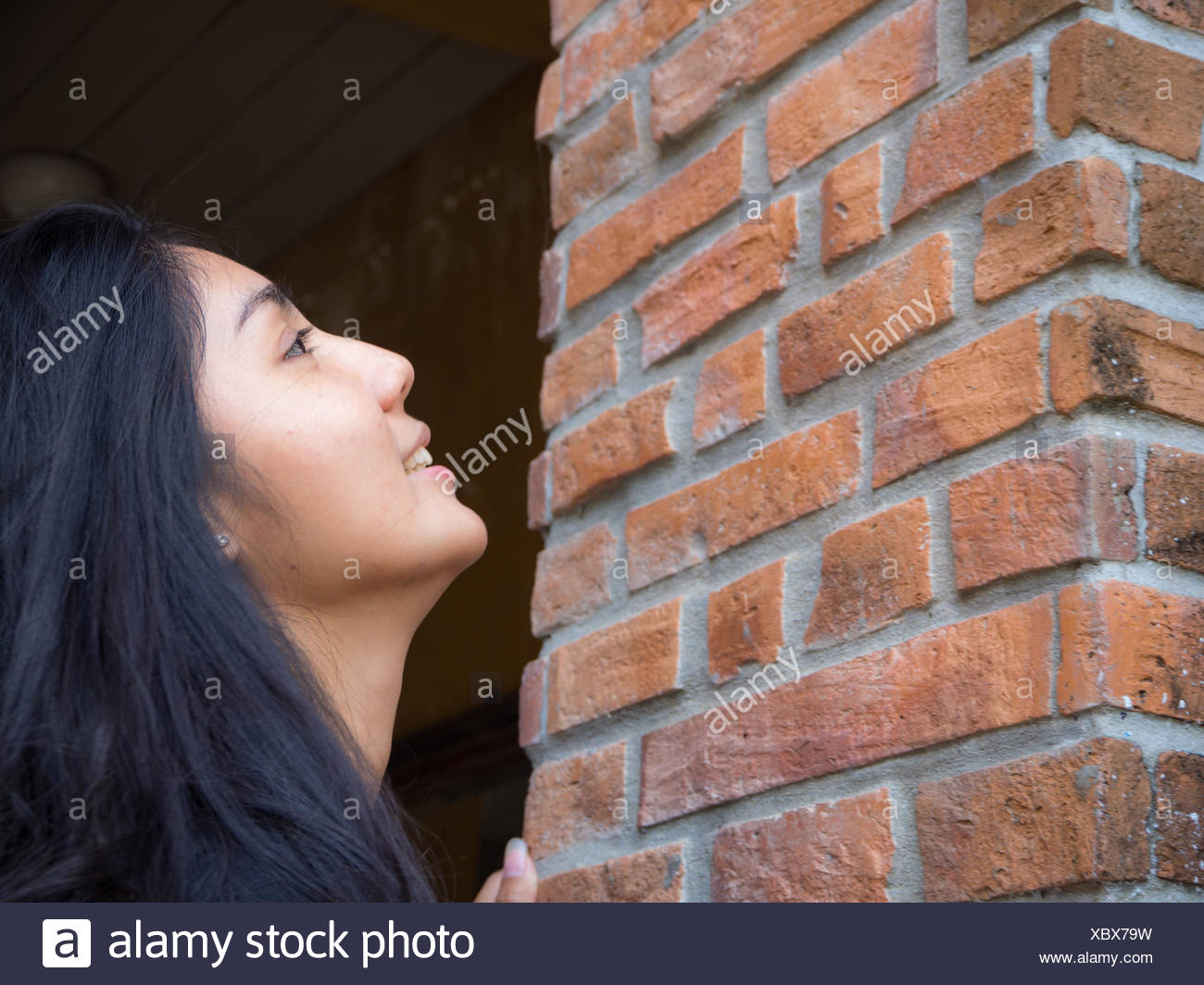 Asian woman looking at the brick wall - Stock Image