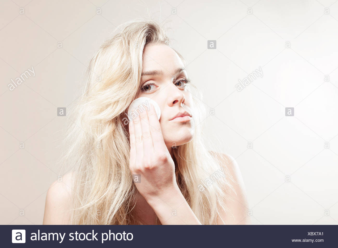 Young woman cleaning her face - Stock Image