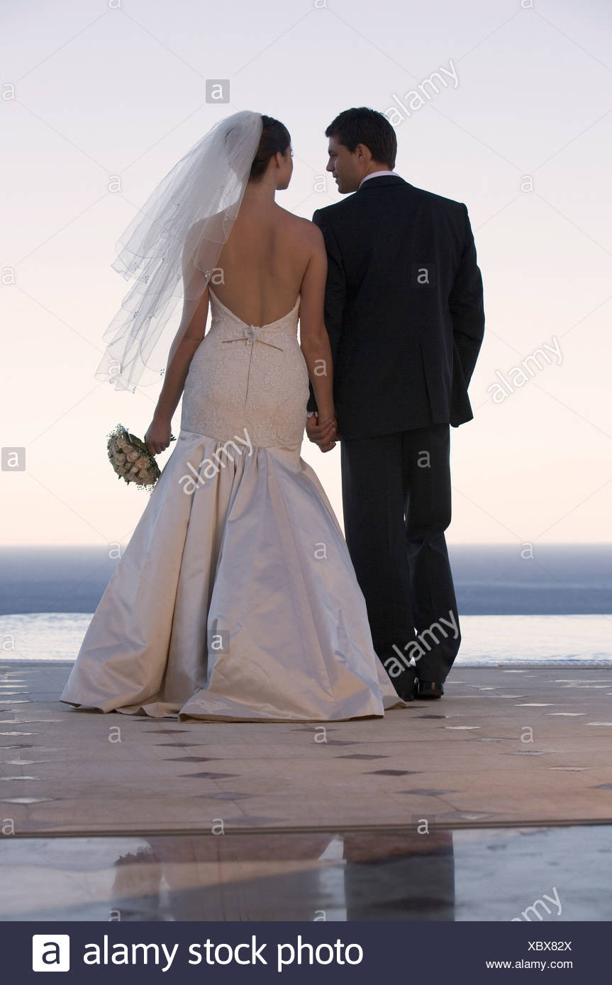 A bride and groom holding hands - Stock Image