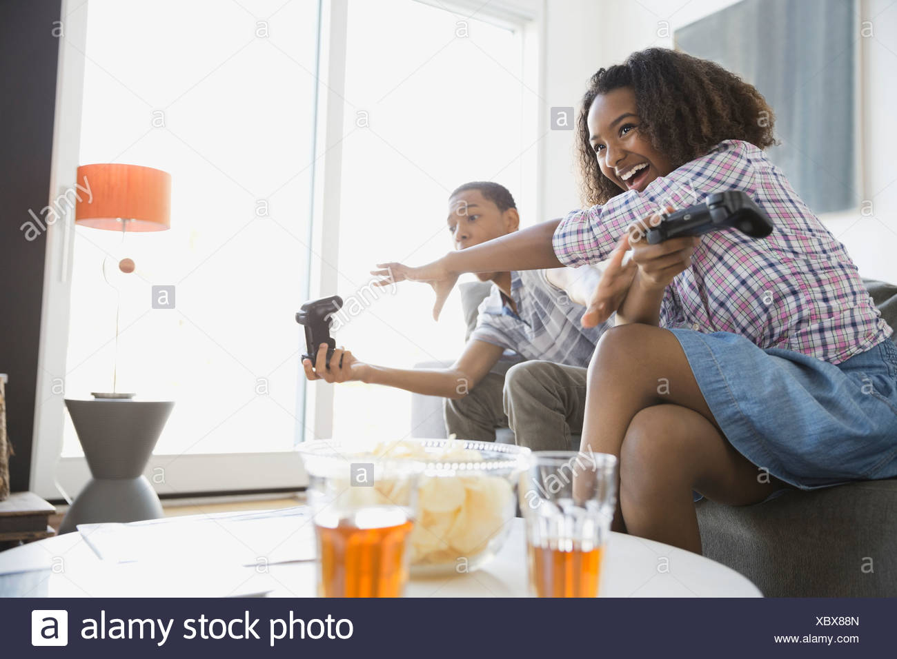 Siblings playing video games at home - Stock Image