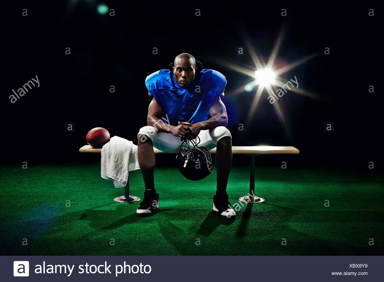 Portrait of american football player sitting on bench - Stock Image