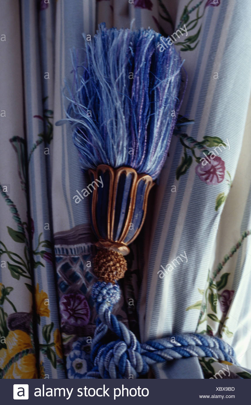 Close-up of blue silk tassel on patterned curtain - Stock Image