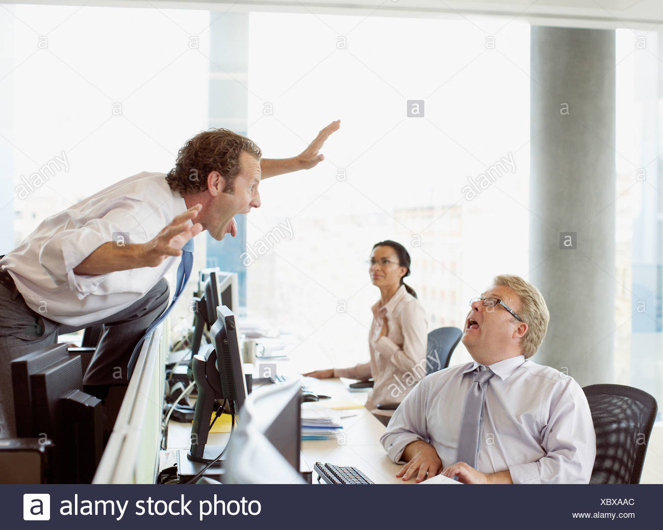 Businessman scaring co-worker in office - Stock Image