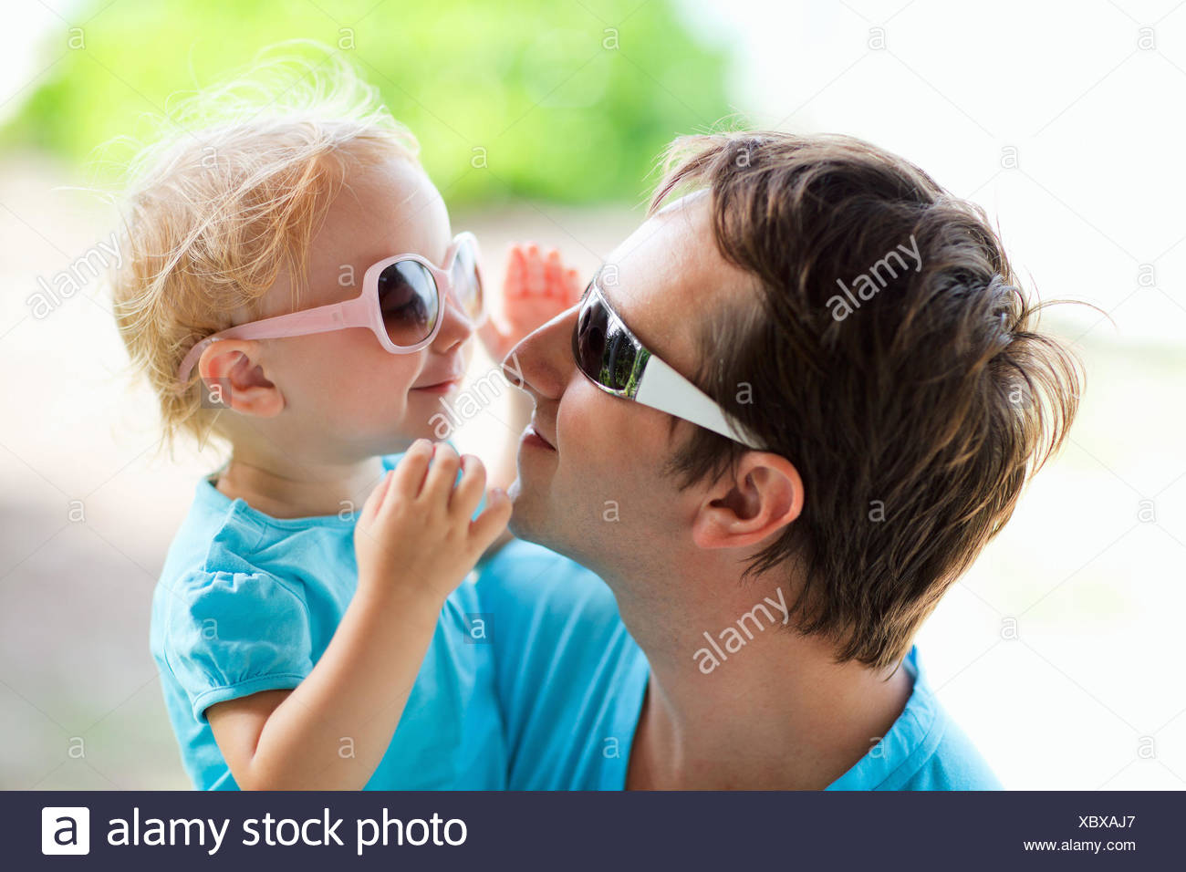 young father and the little daughter on his arm happily looking into each other's eyes through their sunglasses - Stock Image
