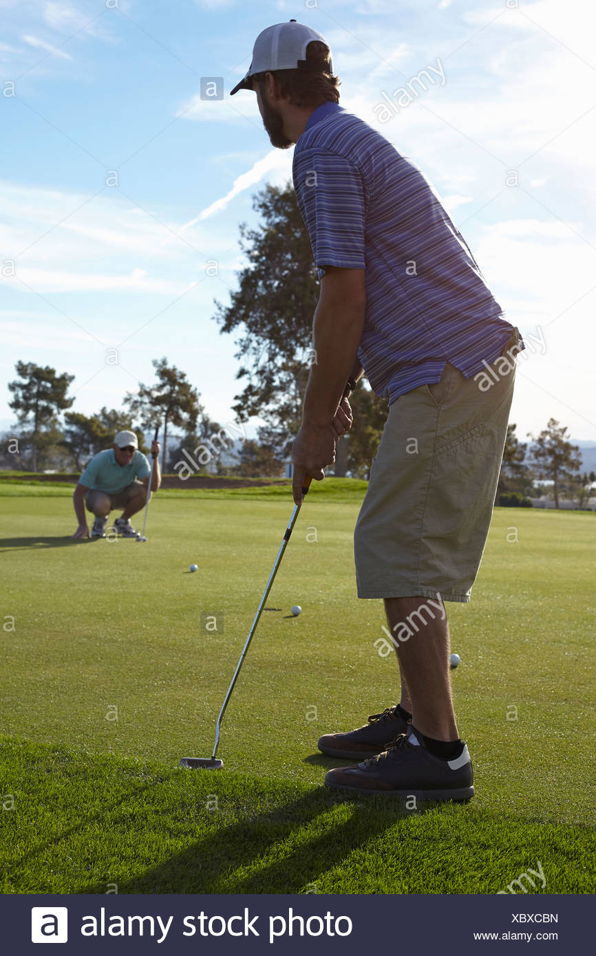 Two male golfers lining up shot on green - Stock Image