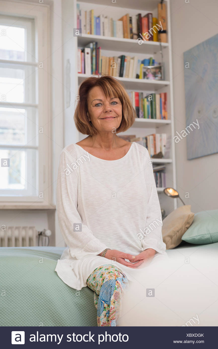Senior woman sitting on bed and smiling, Munich, Bavaria, Germany - Stock Image