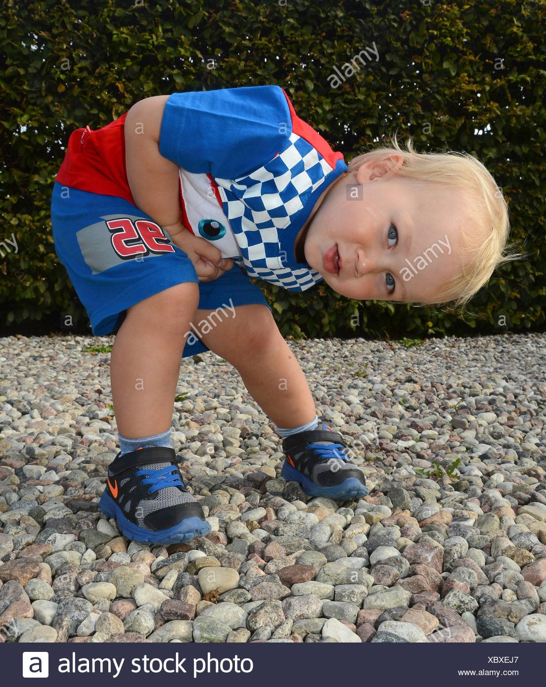 Little blond boy in colorful outfit, two and one-half years old, crouching and discovering his surroundings, Ystad, Sweden - Stock Image