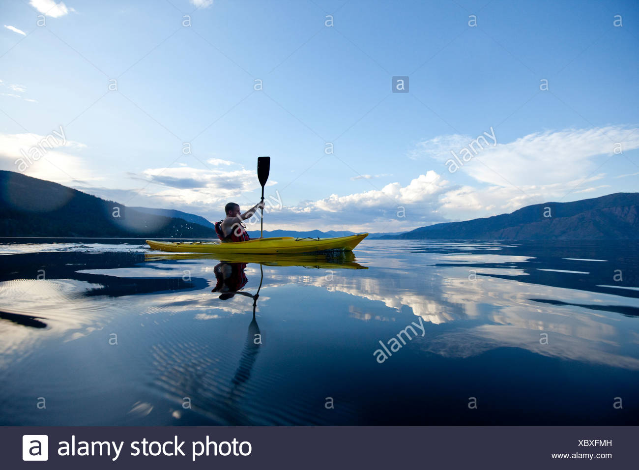 Young man paddles yellow kayak on lake. - Stock Image