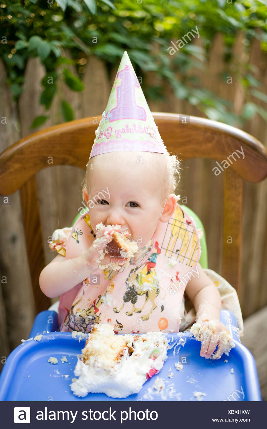 A baby girl celebrates her birthday by eating cake in Philadelphia, Pennsylvania - Stock Image