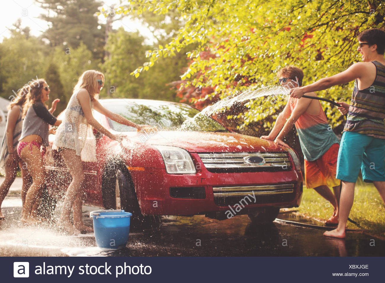 Five friends spraying car with hosepipe - Stock Image