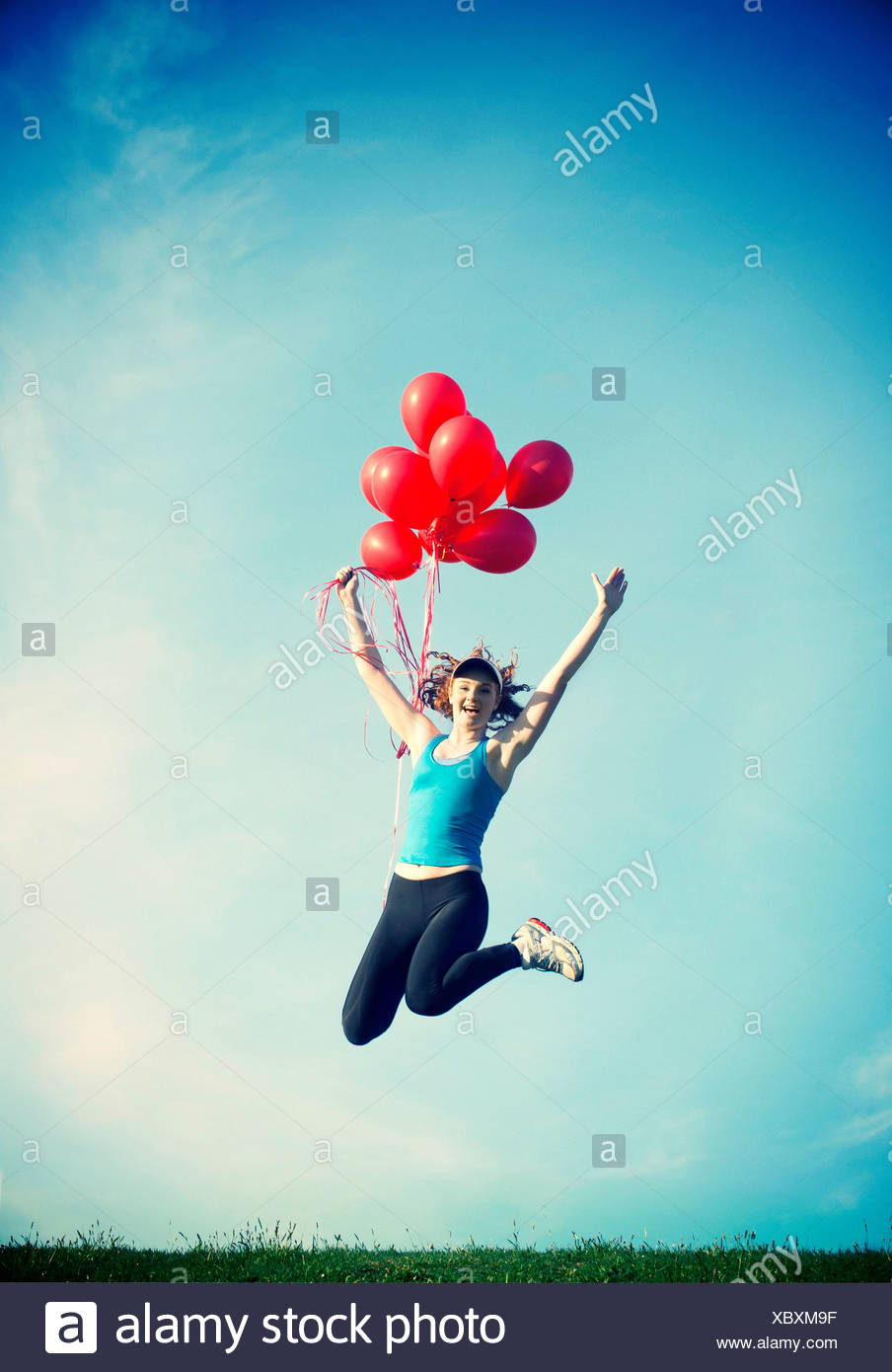 Teenage girl jumping in mid air holding red balloons - Stock Image
