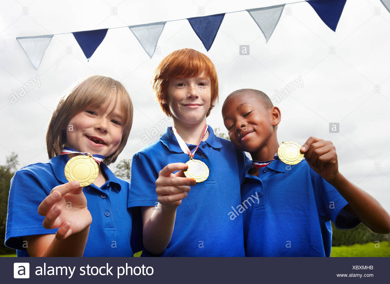 School boys holding medals for sporting achievement - Stock Image