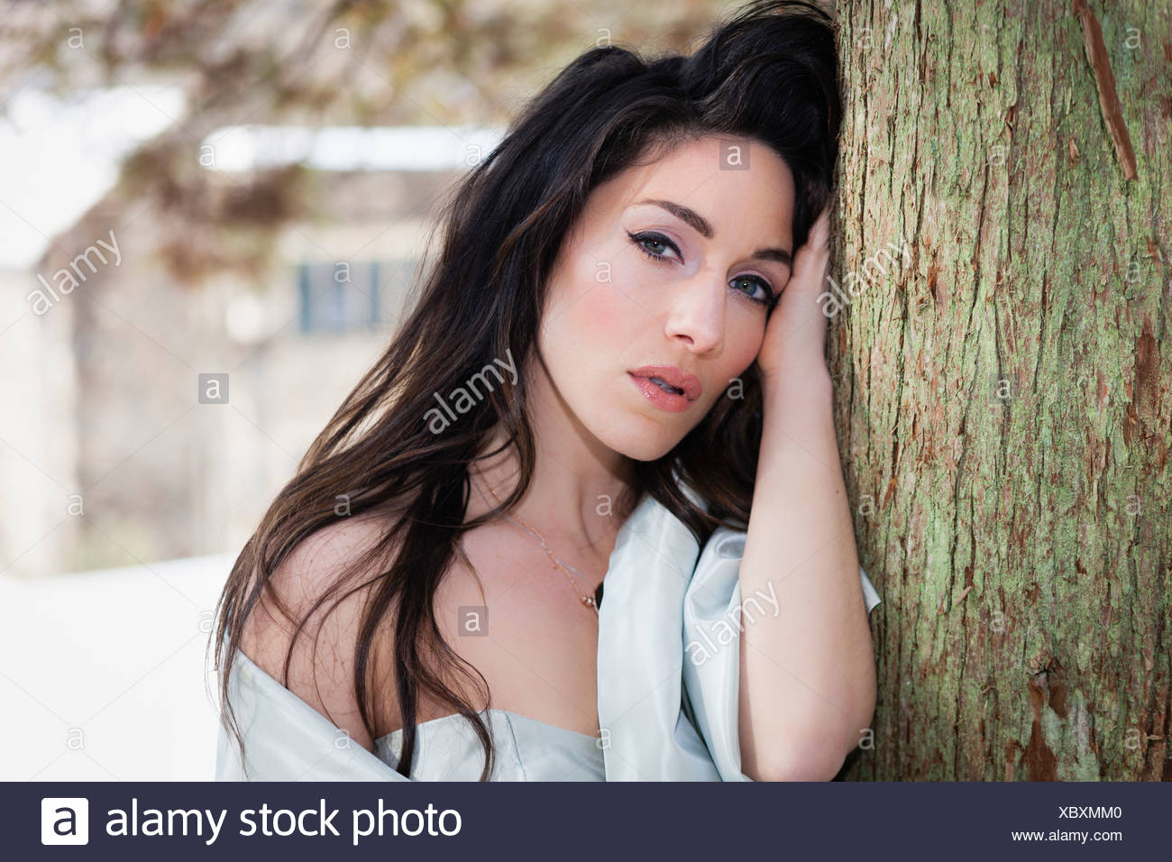 A woman with a light shawl by a tree in snow. - Stock Image