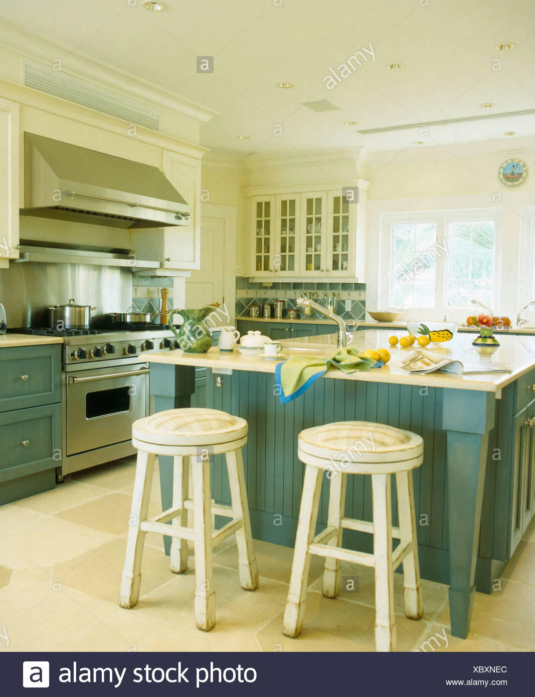 White Wooden Stools At Breakfast Bar On Island Unit In White Bermudan Kitchen With Blue Green Fitted Units And Flagstone Floor Stock Photo Alamy