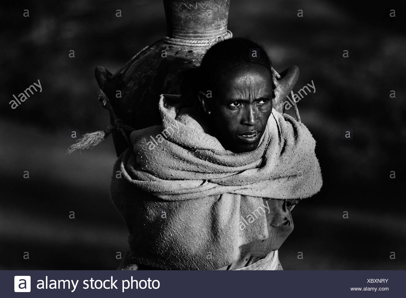 Woman taking a water vat to her house Sekota Ethiopia. - Stock Image