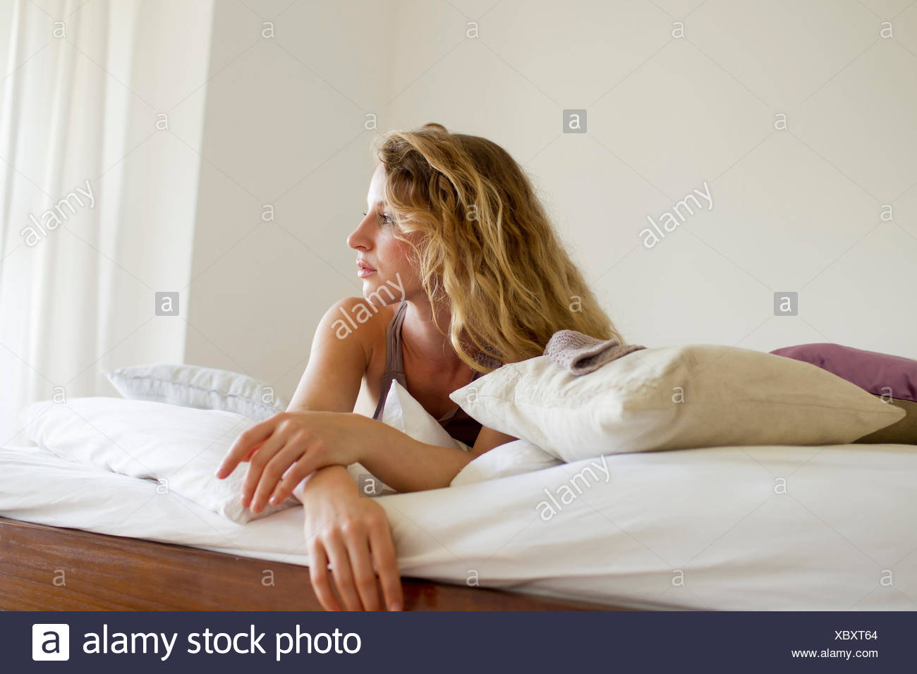 Woman lying in bed day-dreaming - Stock Image