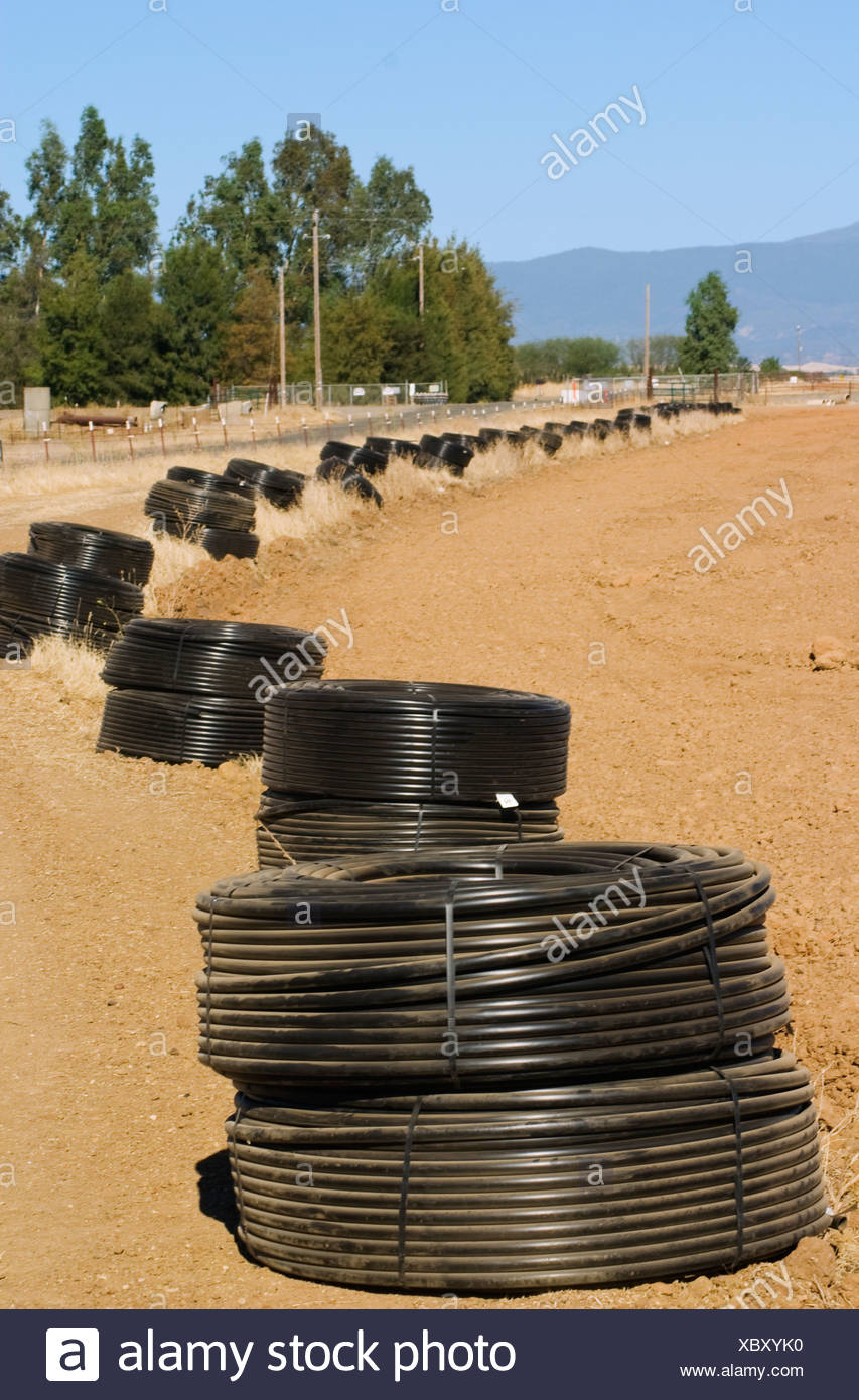 Rolls of drip irrigation tubing laid out along the edge of a field in preparation for the planting of a new almond orchard / USA - Stock Image