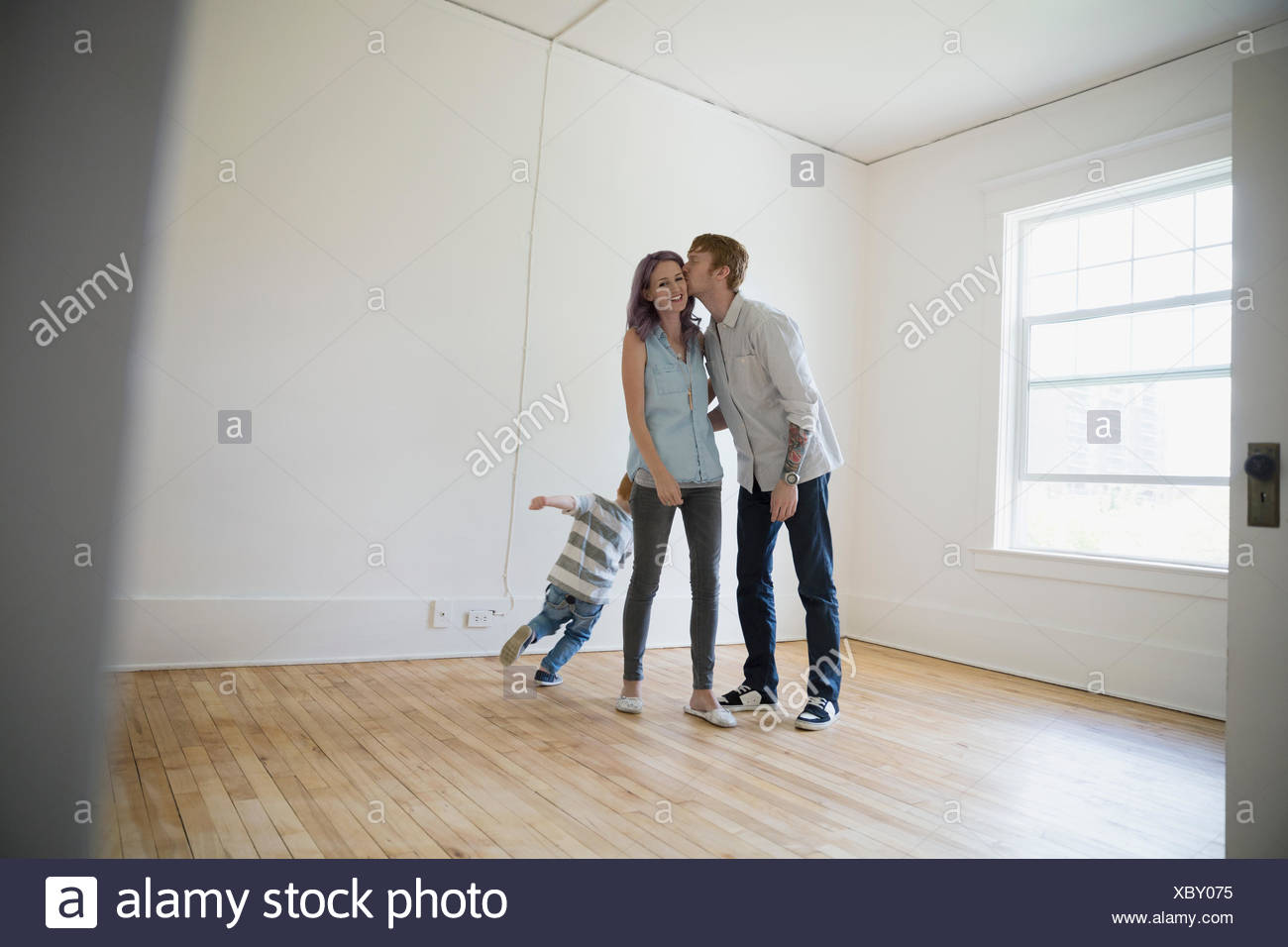 Young family kissing in empty new house - Stock Image