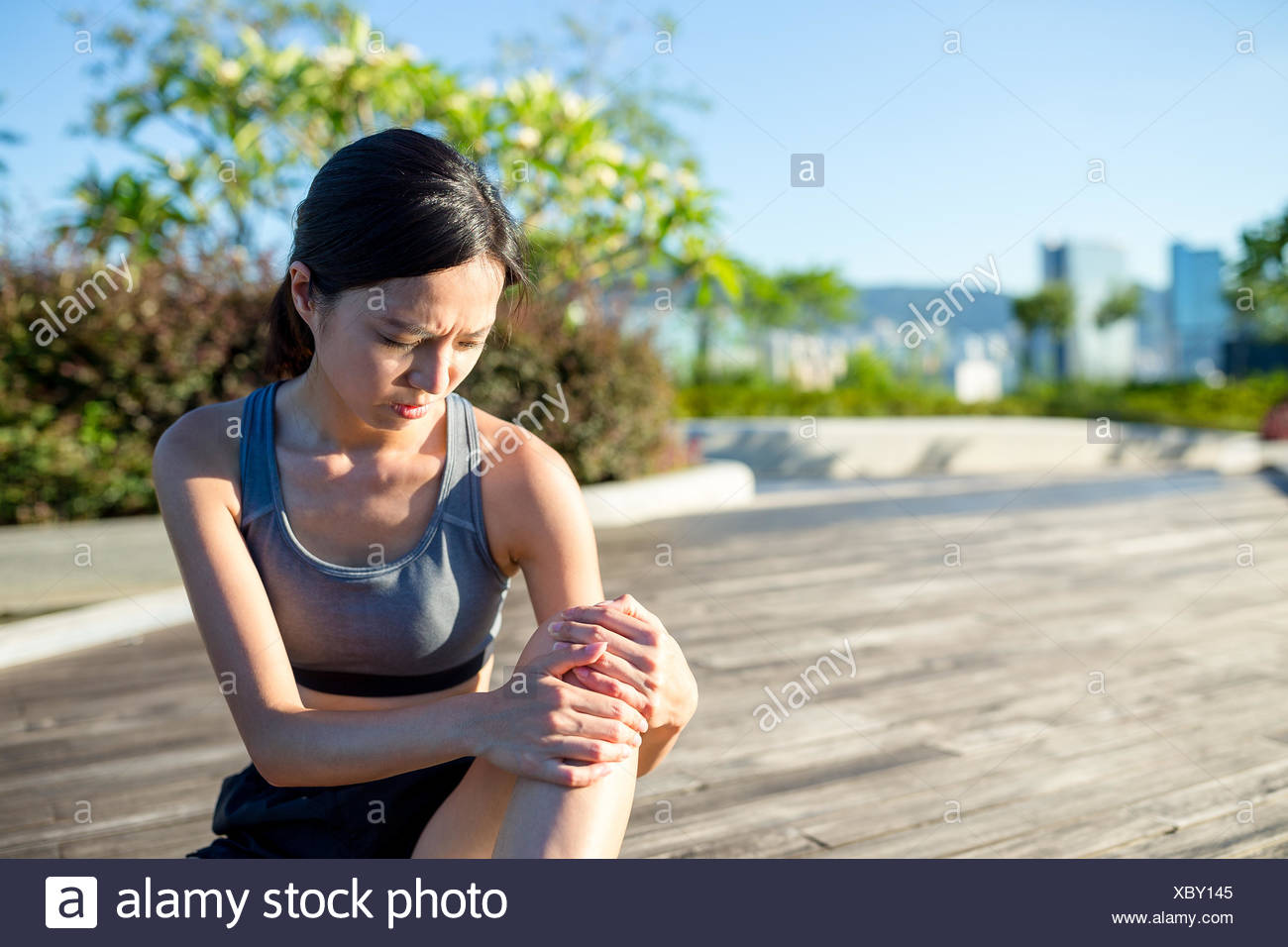 Woman holding painful ankle at park - Stock Image