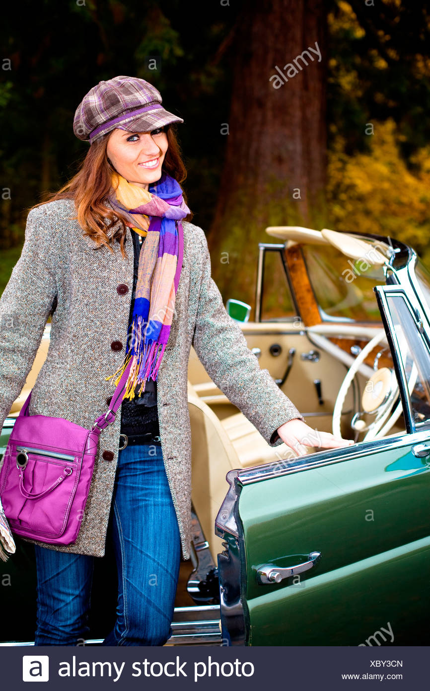 Young woman in front of post-war classic car - Stock Image