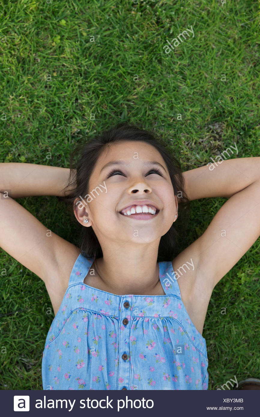 Smiling girl laying in grass hands behind head - Stock Image