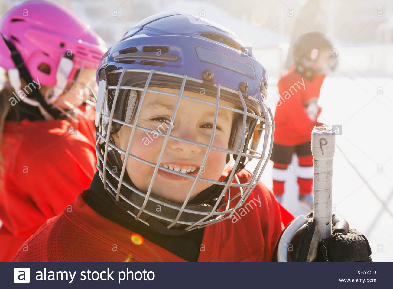 Portrait of cute boy in ice hockey helmet - Stock Image