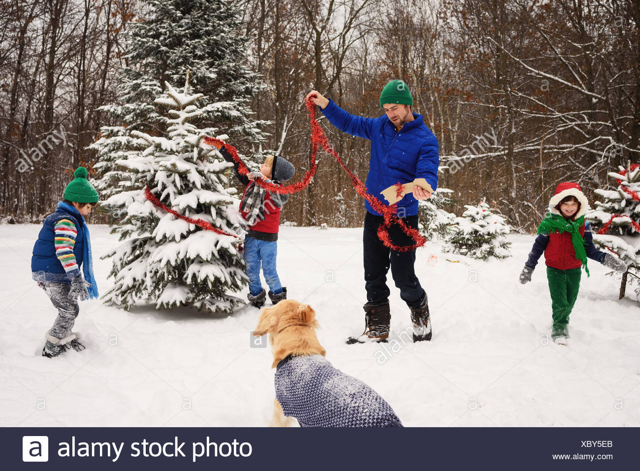 Father and three children decorating a Christmas tree in the garden with golden retriever dog watching Stock Photo