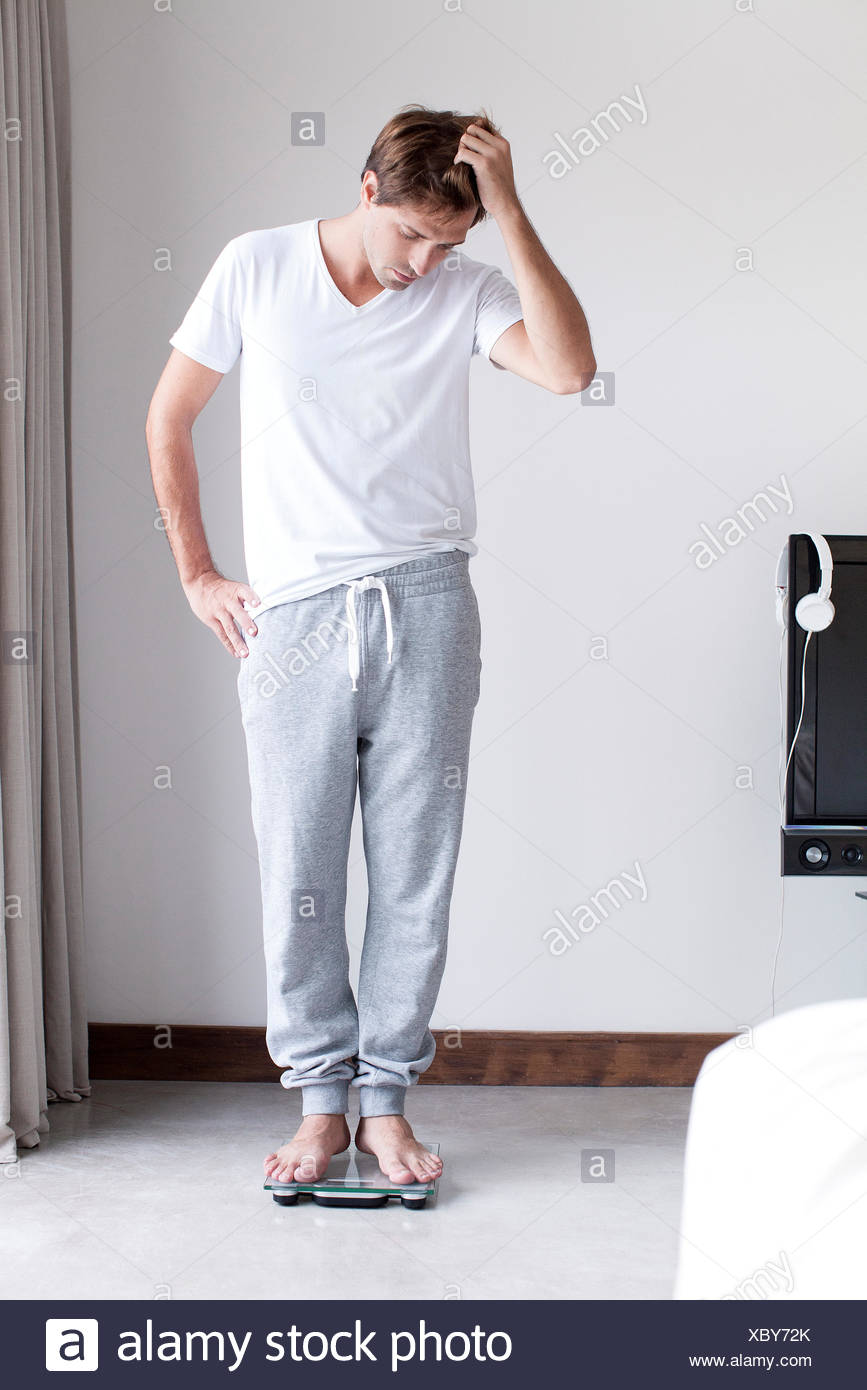Man weighing self on bathroom scale - Stock Image