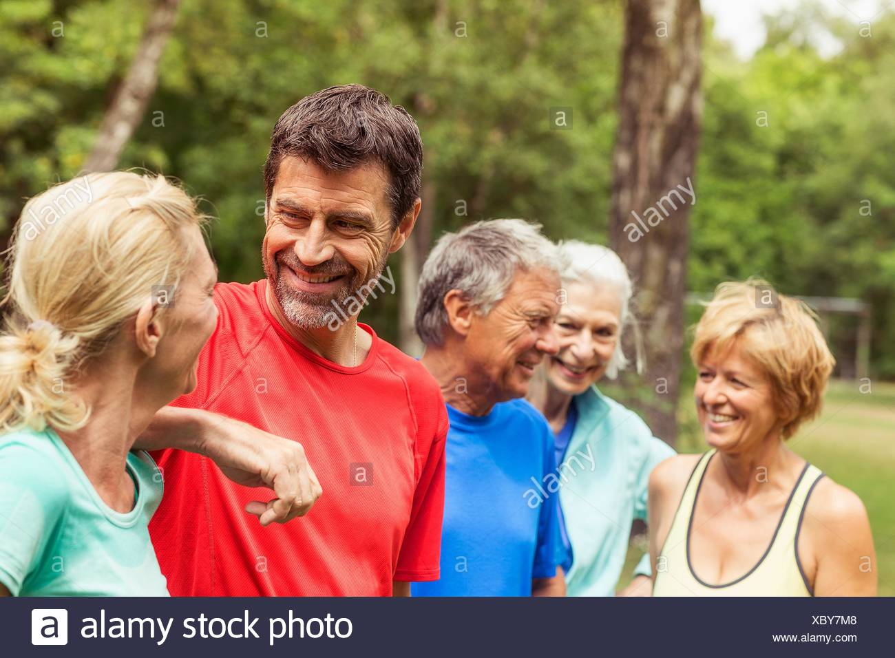 Group of adults outdoors, wearing sports clothing, smiling - Stock Image
