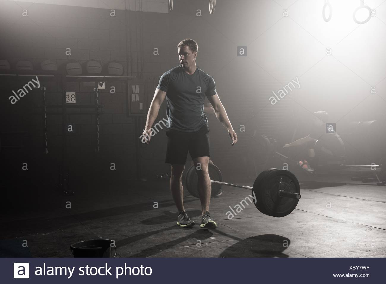 Young man dropping and walking away from barbell - Stock Image