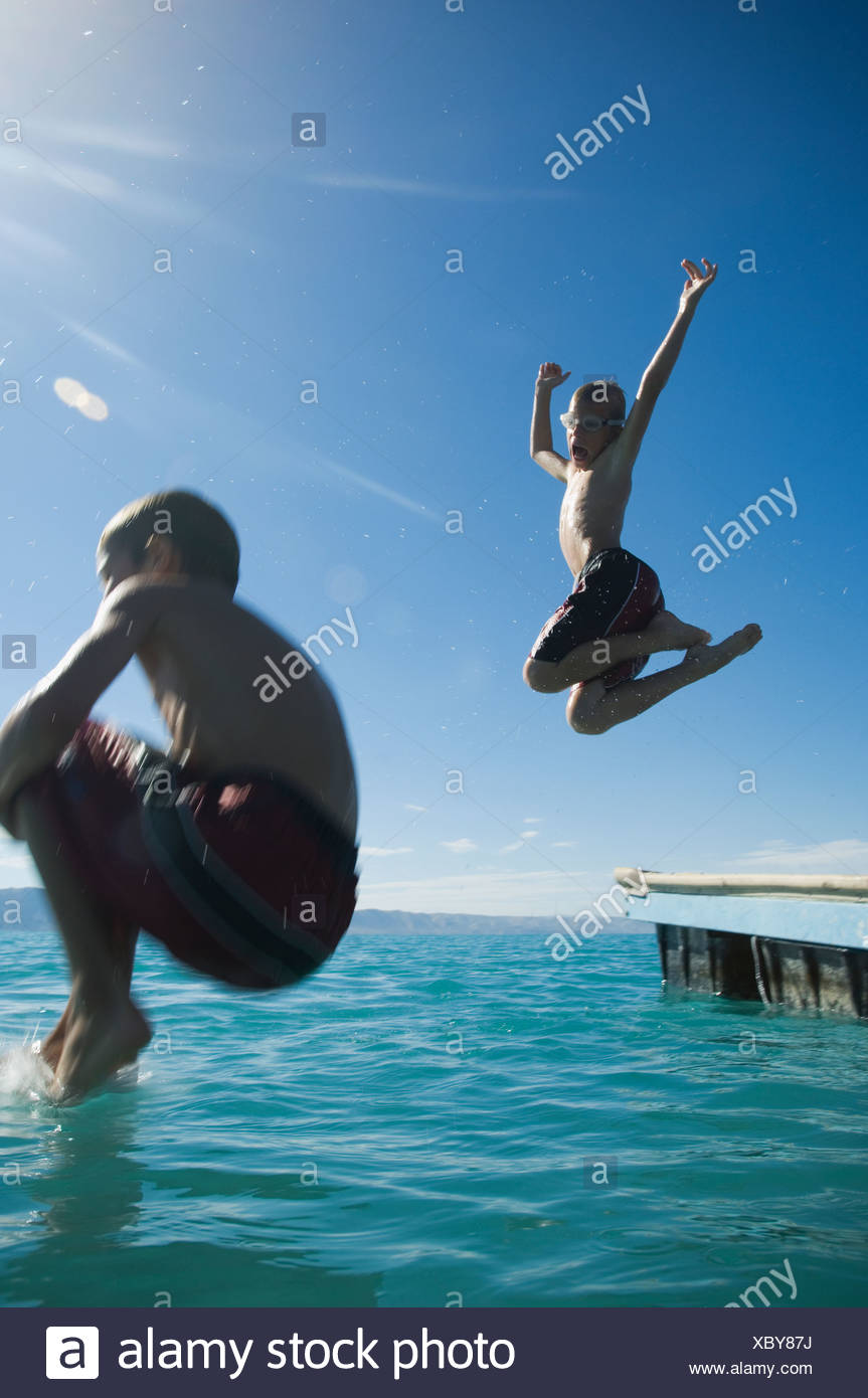 Brothers jumping off dock into lake, Utah, United States - Stock Image