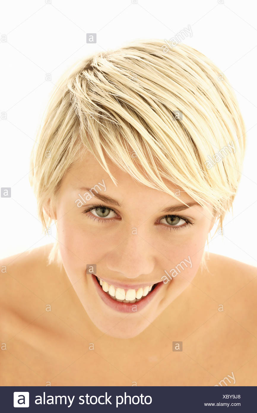 A portrait of a healthy young woman in her early 20s smiling, front - Stock Image