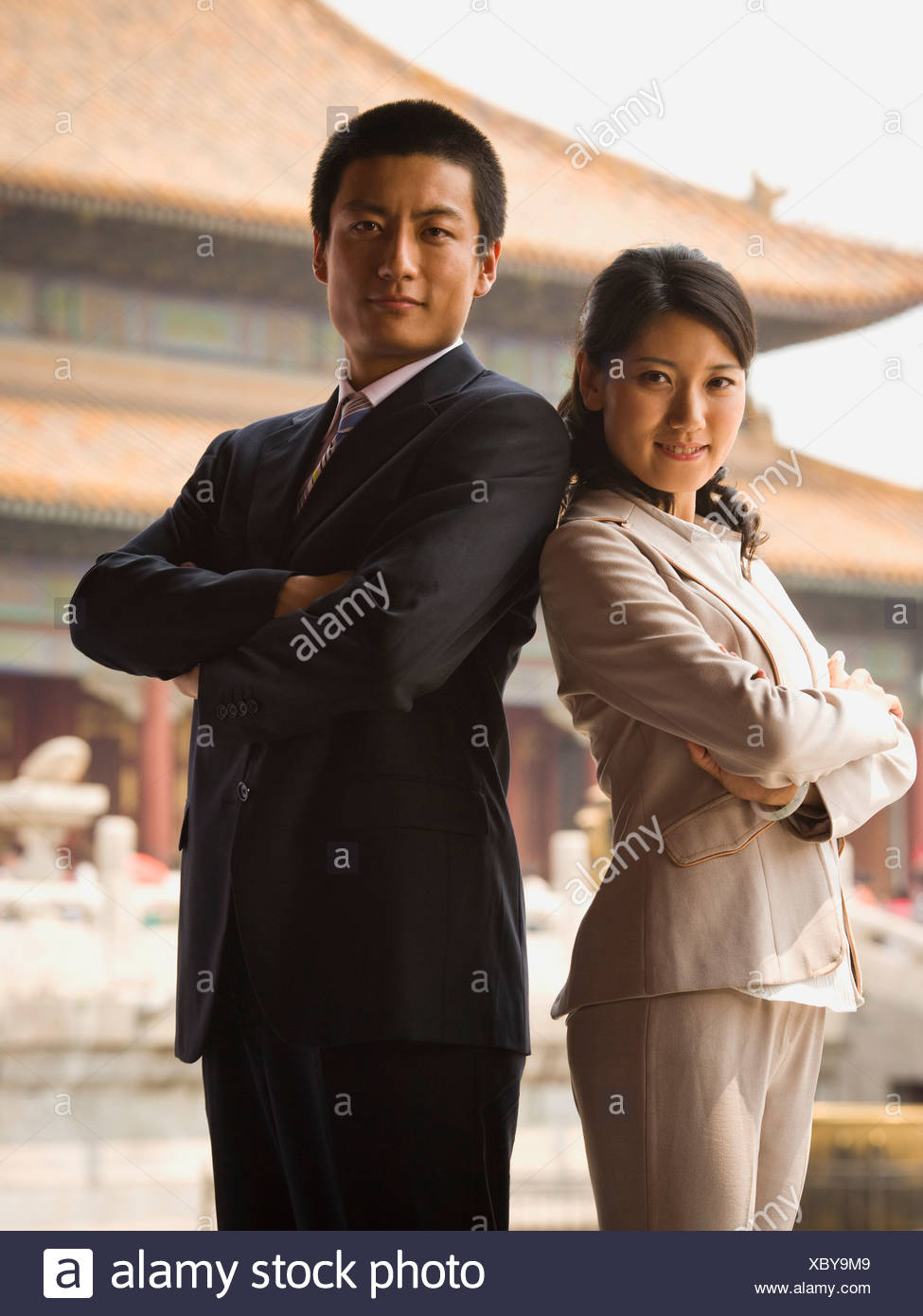 Businessman and woman standing with arms crossed and backs together with pagoda in background - Stock Image