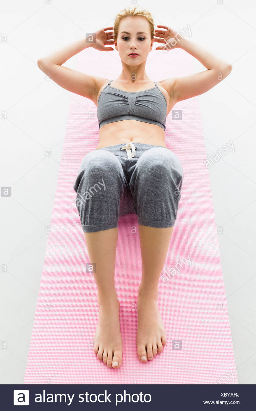 Young woman on exercise mat, doing sit ups - Stock Image