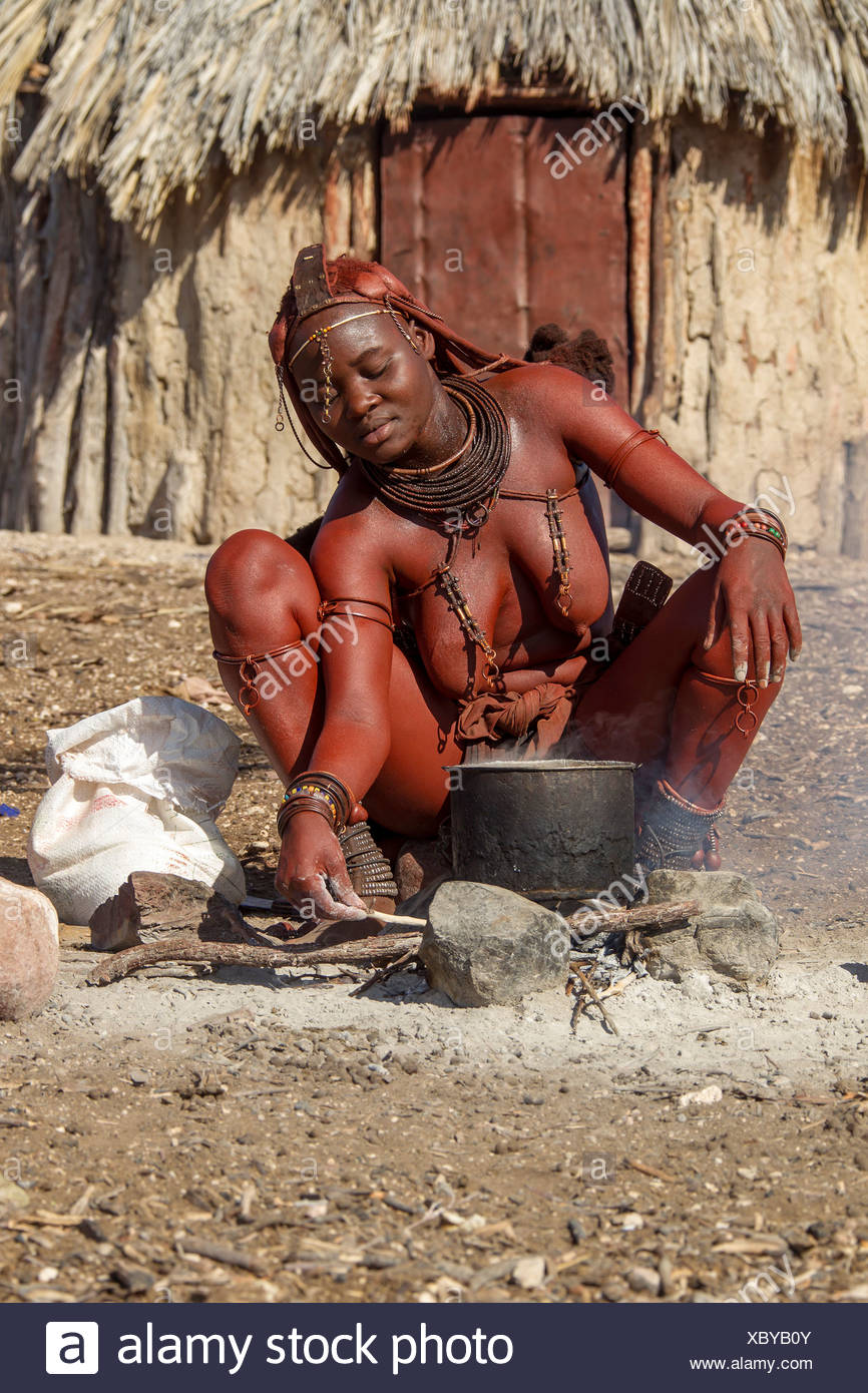 Young Himba woman, sitting at a cooking pit in front of a hut, Kaokoland, Kunene, Namibia - Stock Image