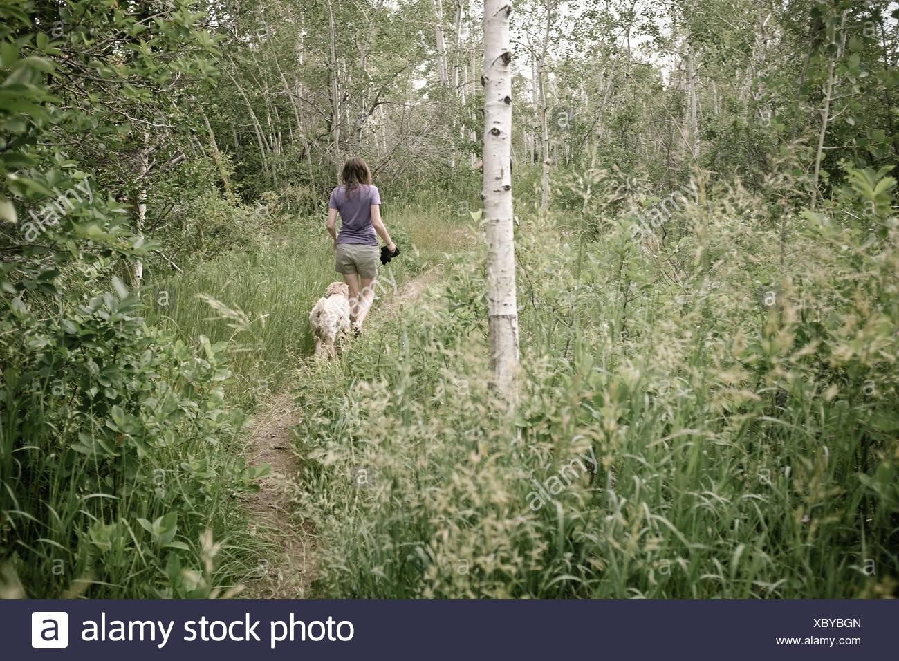 USA, Wyoming, Woman walking with dog - Stock Image