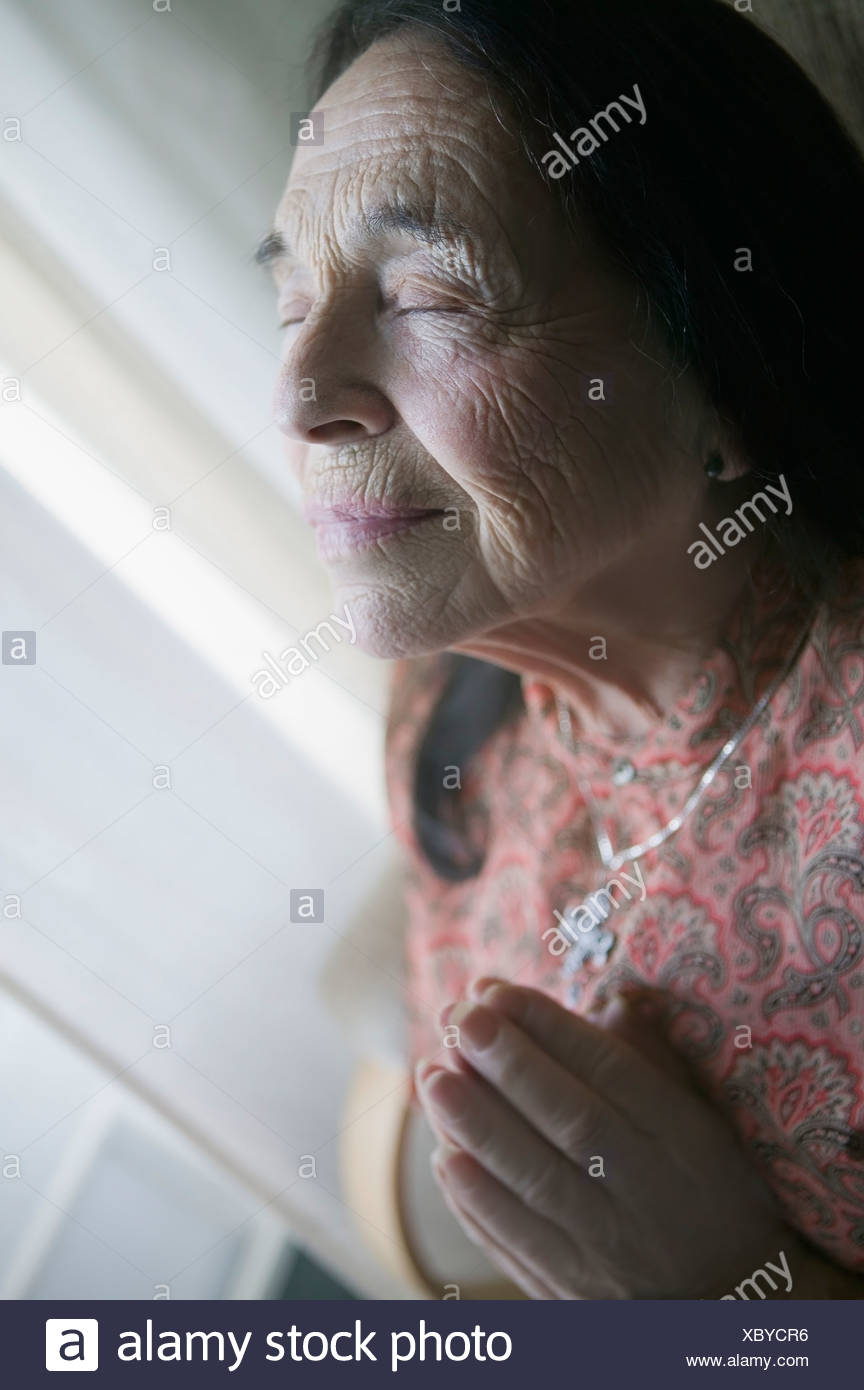 Senior woman praying - Stock Image