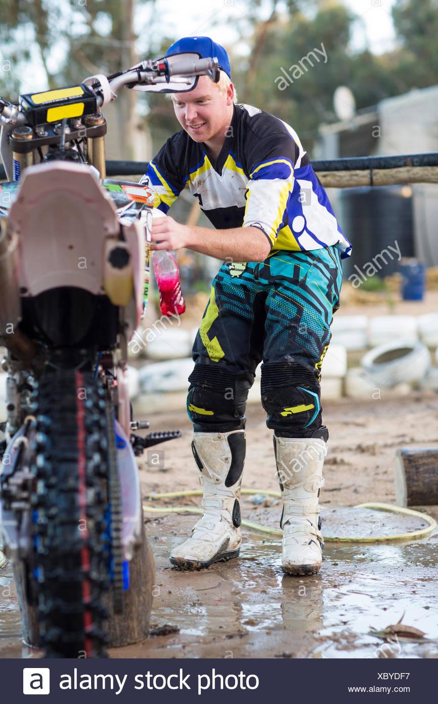 Young male motocross competitor cleaning motorcycle - Stock Image