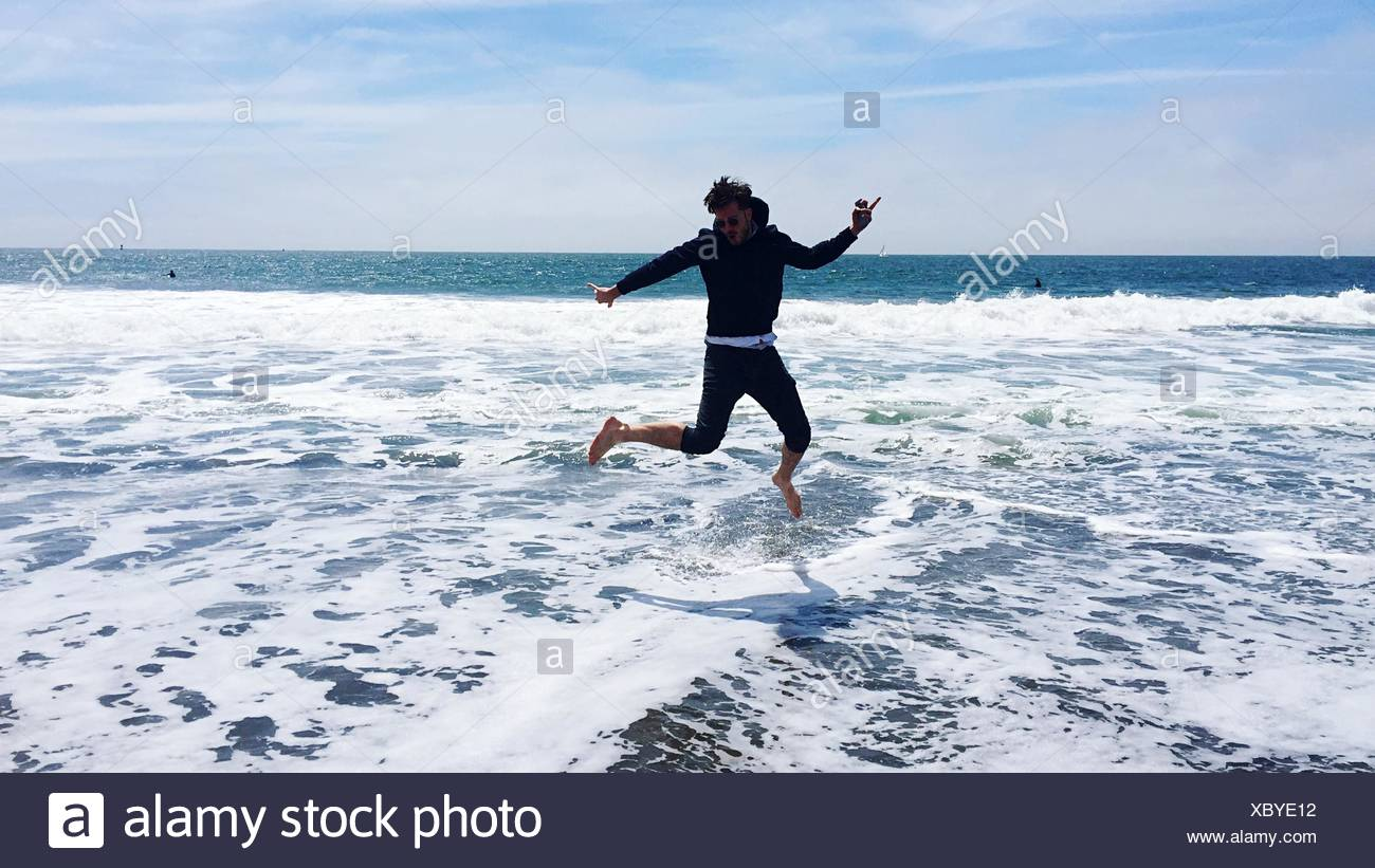Young Man Jumping Over Waves In Sea Against Sky - Stock Image